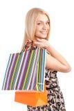 Schöne blonde Frau, die Einkaufstaschen hält Stockfoto
