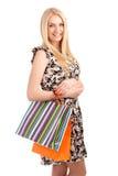 Schöne blonde Frau, die Einkaufstaschen hält Stockbild