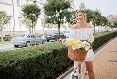 Schöne, blonde Frau, die Fahrrad in einer Stadt fährt Lizenzfreie Stockfotos