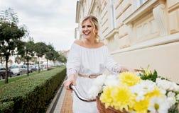 Schöne, blonde Frau, die Fahrrad in einer Stadt fährt Lizenzfreie Stockfotografie