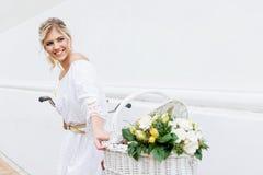 Schöne, blonde Frau, die Fahrrad in einer Stadt fährt Lizenzfreies Stockfoto