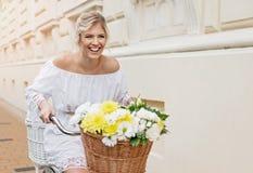Schöne, blonde Frau, die Fahrrad in einer Stadt fährt Stockbild