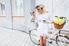 Schöne, blonde Frau, die Fahrrad in einer Stadt mit ihrem Hund fährt Stockfotografie