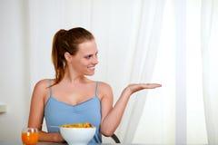 Schöne blonde Frau, die Frühstück isst Stockbild