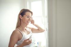 Schöne blonde Frau, die Gesichtscreme aufträgt Lizenzfreies Stockfoto