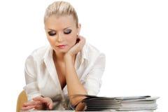 Schöne blonde Frau, die glatte Zeitschriften liest Lizenzfreies Stockfoto