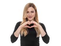 Schöne blonde Frau, die Herzzeichen mit ihren Händen zeigt Stockbild