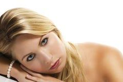 Schöne blonde Frau, die ihren Kopf auf eine Tabelle legt Lizenzfreie Stockfotos