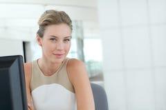 Schöne blonde Frau, die im Büro sitzt Stockfotos