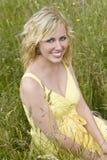 Schöne blonde Frau, die im hohen Gras sitzt Stockbilder