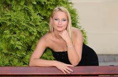 Schöne blonde Frau, die im Park aufwirft Lizenzfreie Stockfotos