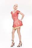 Schöne blonde Frau, die im roten kurzen Kleid steht Stockbild