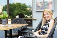 Schöne blonde Frau, die im Straßenkaffee sitzt Lizenzfreie Stockfotos