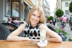 Schöne blonde Frau, die im Straßenkaffee sitzt Lizenzfreies Stockfoto