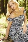 Schöne blonde Frau, die im Wald sitzt. Sommersonne. Lizenzfreies Stockfoto