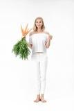 Schöne blonde Frau, die Kaninchen zeigt und frische Karotte mit Grünblättern auf weißem Hintergrund hält Gesundheit und Diät Lizenzfreies Stockfoto