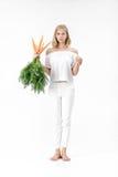 Schöne blonde Frau, die Kaninchen zeigt und frische Karotte mit Grünblättern auf weißem Hintergrund hält Gesundheit und Diät Stockbild
