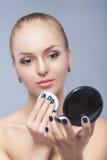Schöne blonde Frau, die kosmetischen Schwamm hält und im Taschenspiegel auf grauem Hintergrund schaut Stockbild