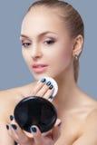 Schöne blonde Frau, die kosmetischen Schwamm hält und im Taschenspiegel auf grauem Hintergrund schaut Lizenzfreies Stockfoto