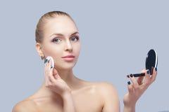 Schöne blonde Frau, die kosmetischen Schwamm hält und im Taschenspiegel auf grauem Hintergrund schaut Stockfoto
