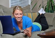 Schöne blonde Frau, die Laptop auf Couch verwendet Lizenzfreies Stockbild