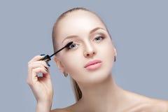 Schöne blonde Frau, die Make-up auf Gesicht auf grauem Hintergrund anwendet Perfektes Make-up Bürste der Wimperntusche Lizenzfreie Stockfotografie