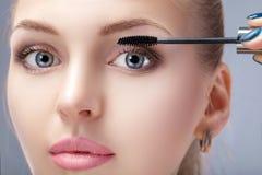Schöne blonde Frau, die Make-up auf Gesicht auf grauem Hintergrund anwendet Perfektes Make-up Bürste der Wimperntusche Lizenzfreie Stockbilder
