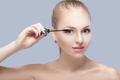 Schöne blonde Frau, die Make-up auf Gesicht auf grauem Hintergrund anwendet Perfektes Make-up Bürste der Wimperntusche Lizenzfreies Stockfoto