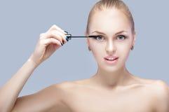 Schöne blonde Frau, die Make-up auf Gesicht auf grauem Hintergrund anwendet Perfektes Make-up Bürste der Wimperntusche Lizenzfreies Stockbild