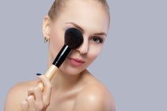 Schöne blonde Frau, die Make-upbürste auf einem grauen Hintergrund hält Stockfotografie