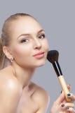 Schöne blonde Frau, die Make-upbürste auf einem grauen Hintergrund hält Lizenzfreie Stockfotografie