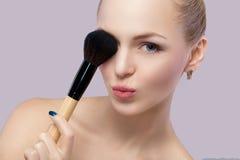 Schöne blonde Frau, die Make-upbürste auf einem grauen Hintergrund hält Stockbilder