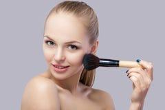 Schöne blonde Frau, die Make-upbürste auf einem grauen Hintergrund hält Stockbild