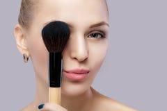 Schöne blonde Frau, die Make-upbürste auf einem grauen Hintergrund hält Lizenzfreie Stockfotos