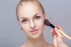Schöne blonde Frau, die Make-upbürste auf einem grauen Hintergrund hält Frau, die Blusher anwendet Stockbilder