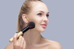 Schöne blonde Frau, die Make-upbürste auf einem grauen Hintergrund hält Frau, die Blusher anwendet Stockfotos