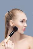 Schöne blonde Frau, die Make-upbürste auf einem grauen Hintergrund hält Frau, die Blusher anwendet Lizenzfreies Stockbild