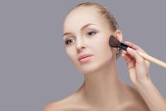 Schöne blonde Frau, die Make-upbürste auf einem grauen Hintergrund hält Frau, die Blusher anwendet Lizenzfreies Stockfoto