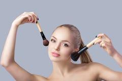 Schöne blonde Frau, die Make-upbürste auf grauem Hintergrund hält Abschluss oben Lizenzfreies Stockbild