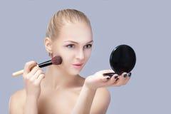Schöne blonde Frau, die Make-upbürste hält und im Spiegel auf einem grauen Hintergrund schaut Lizenzfreies Stockbild