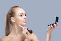 Schöne blonde Frau, die Make-upbürste hält und im Spiegel auf einem grauen Hintergrund schaut Lizenzfreie Stockfotografie