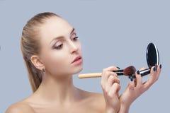 Schöne blonde Frau, die Make-upbürste hält und im Spiegel auf einem grauen Hintergrund schaut Stockfoto