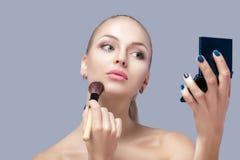 Schöne blonde Frau, die Make-upbürste hält und im Spiegel auf einem grauen Hintergrund schaut Lizenzfreie Stockbilder