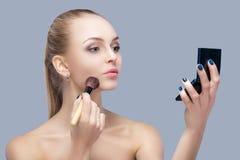 Schöne blonde Frau, die Make-upbürste hält und im Spiegel auf einem grauen Hintergrund schaut Lizenzfreie Stockfotos