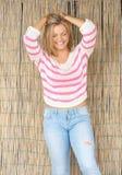 Schöne blonde Frau, die mit den Händen im Haar lacht Lizenzfreie Stockfotografie