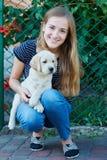 Schöne blonde Frau, die mit einem weißen Labrador-Welpen spielt Stockbild