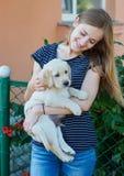 Schöne blonde Frau, die mit einem Welpen Labrador spielt Lizenzfreie Stockfotos