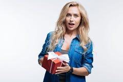 Schöne blonde Frau, die mit einer Geschenkbox aufwirft Stockfoto