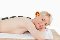Schöne blonde Frau, die mit heißen Steinen sich entspannt Stockfotografie