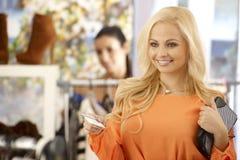 Schöne blonde Frau, die mit Kreditkarte zahlt Stockbilder